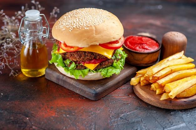 Vista frontal sabrosa hamburguesa de carne con papas fritas sobre fondo oscuro