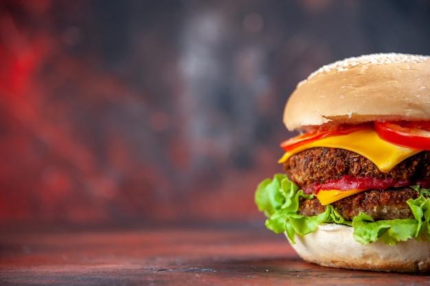 Vista frontal sabrosa hamburguesa de carne con queso y ensalada en el fondo oscuro