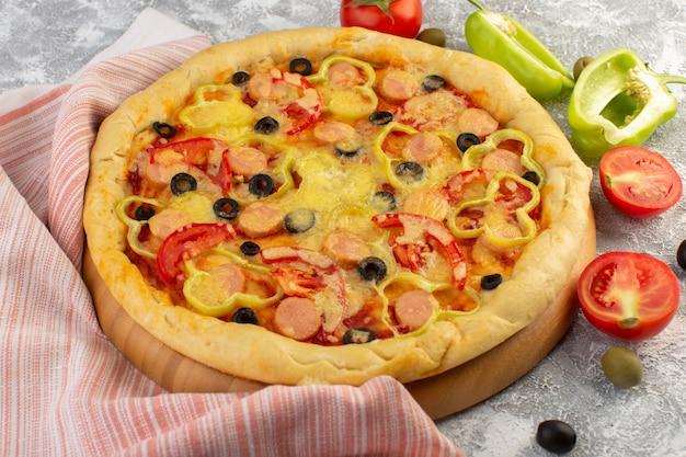 Vista frontal sabrosa pizza con queso con aceitunas negras, salchichas y tomates rojos sobre gris d