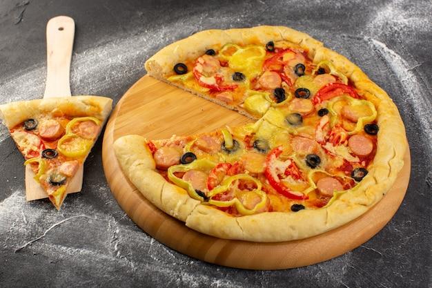 Vista frontal sabrosa pizza con queso con tomates rojos, aceitunas negras, pimientos y salchichas en la oscuridad.