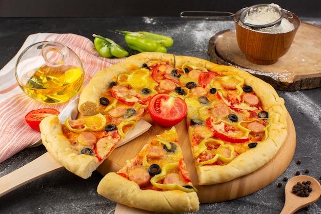 Vista frontal sabrosa pizza con queso con tomates rojos, aceitunas negras y salchichas junto con aceite y harina en la oscuridad
