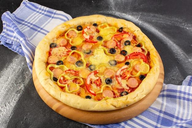 Vista frontal sabrosa pizza con queso con tomates rojos, aceitunas negras y salchichas en la oscuridad.