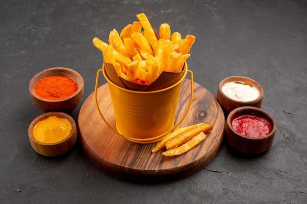 Vista frontal sabrosas papas fritas con salsas en el espacio oscuro
