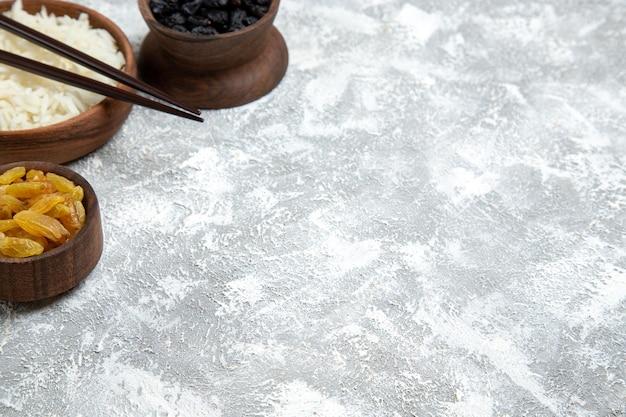 Vista frontal sabroso arroz cocido dentro de la placa marrón con pasas en el espacio en blanco