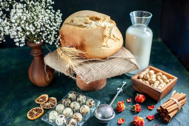 Vista frontal sabroso pan fresco con nueces y leche en superficie oscura