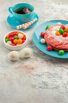 Vista frontal sabroso pastel rosa con caramelos y taza de té sobre fondo blanco pastel de color de postre de caramelo de arco iris de golosinas