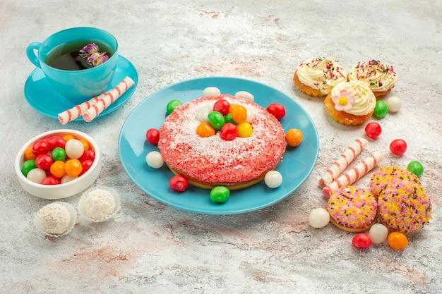 Vista frontal sabroso pastel rosa con deliciosos pasteles de galleta y té sobre fondo blanco pastel de color de postre de caramelo de arco iris de golosinas