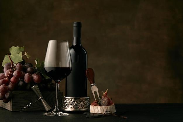 Vista frontal del sabroso plato de frutas de uvas con la botella de vino, queso y copa de vino en la oscuridad