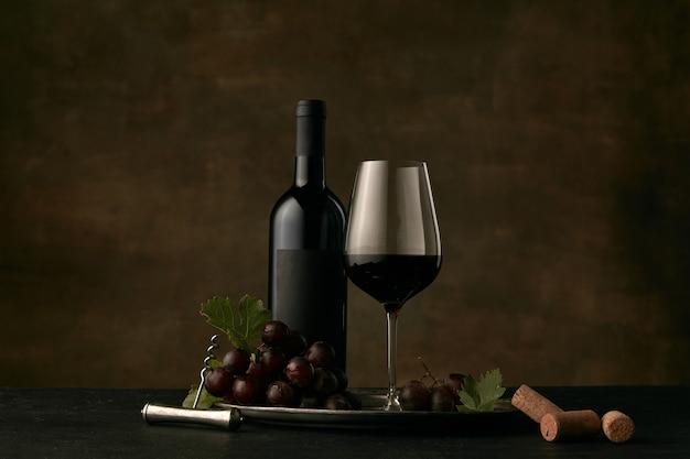 Vista frontal del sabroso plato de frutas de uvas con la botella de vino, queso, frutas y vidrio sobre fondo oscuro