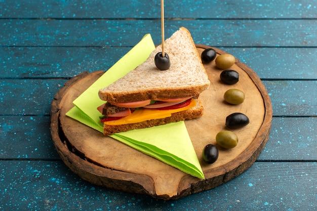 Vista frontal sabroso sándwich con jamón de queso dentro con aceitunas en el escritorio de madera azul