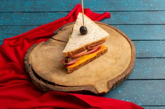 Vista frontal sabroso sándwich con jamón de queso dentro de un escritorio de madera azul