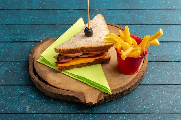 Vista frontal sabroso sándwich con jamón de queso dentro con papas fritas en madera azul