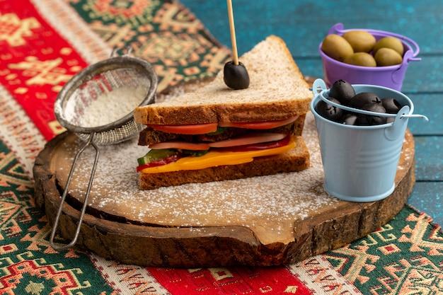 Vista frontal sabroso sándwich de tostadas con jamón de queso en el interior junto con cestas de harina con aceitunas en azul