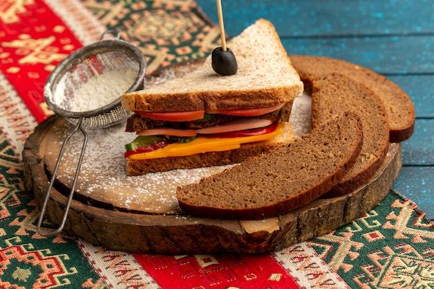 Vista frontal sabroso sándwich de tostadas con jamón de queso en el interior junto con hogazas de pan de harina en azul