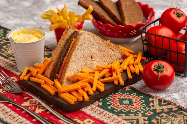 Vista frontal sabroso sándwich de tostadas con jamón de queso junto con papas fritas tomates crema agria en blanco