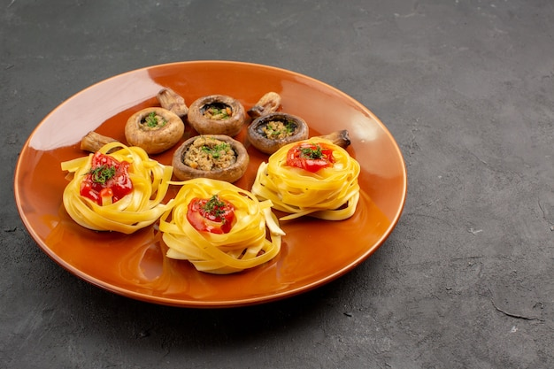 Vista frontal de sabrosos champiñones cocidos con pasta de masa en la mesa oscura comida cena comida