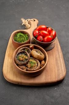 Vista frontal sabrosos champiñones cocidos con tomates frescos en la mesa oscura comida salvaje madura