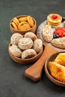 Vista frontal sabrosos panqueques con diferentes dulces en postre de azúcar de pastel de superficie oscura