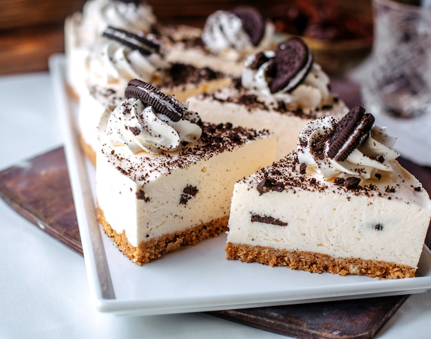 Vista frontal sabrosos pasteles de queso oreo dentro de un plato blanco sobre la superficie marrón