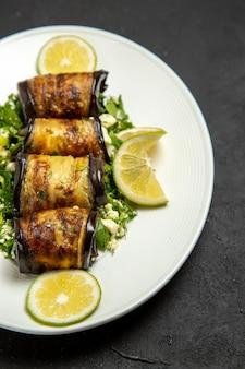 Vista frontal de sabrosos rollos de berenjena con rodajas de limón en la superficie oscura cocinar comida cena plato de aceite de cítricos