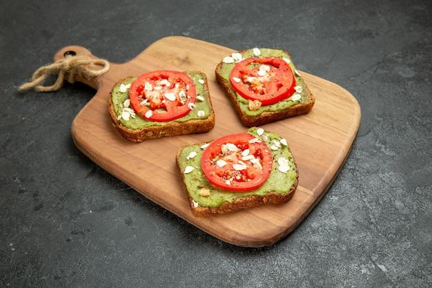 Vista frontal sabrosos sándwiches de aguacate con tomates rojos en rodajas