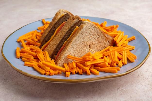 Vista frontal sabrosos sándwiches de tostadas con jamón de queso junto con papas fritas dentro de la placa en blanco