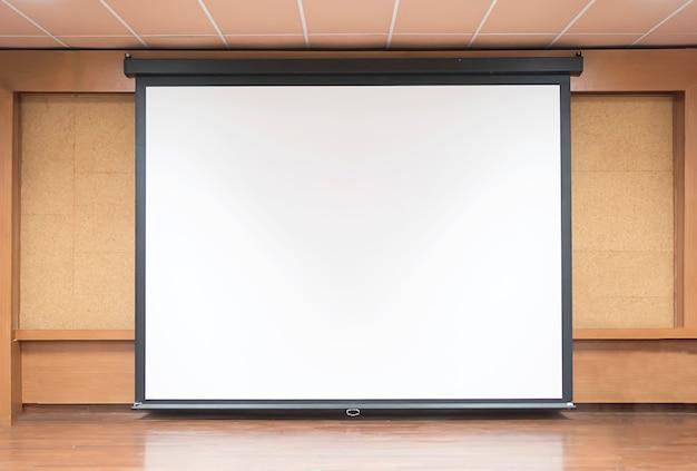 Vista frontal de la sala de conferencias con pantalla de proyector blanca vacía