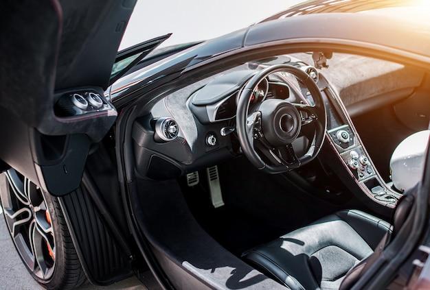 Vista frontal del salón del automóvil deportivo negro, rueda negra con color plateado metálico, dirección, puerta abierta.