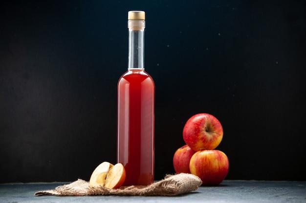 Vista frontal de la salsa de manzana roja en botella con manzanas frescas sobre una superficie oscura