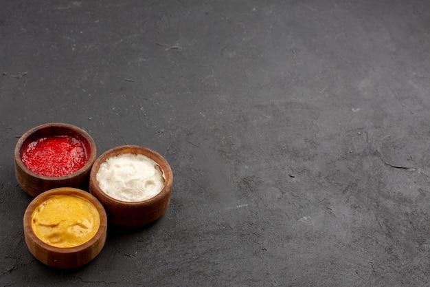 Vista frontal de salsa de tomate y mostaza con mayyonaise dentro de pequeñas ollas en el espacio oscuro