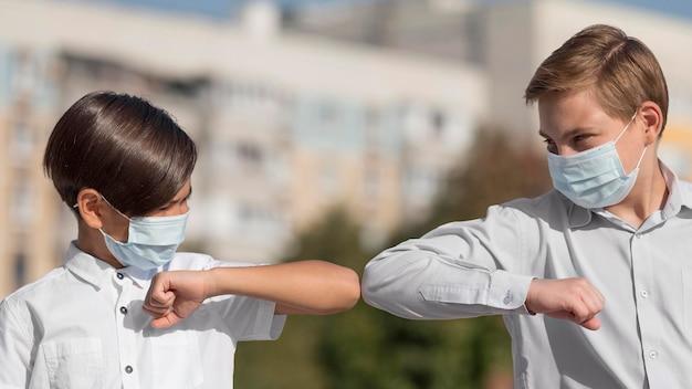 Vista frontal del saludo de los niños con golpe de codo
