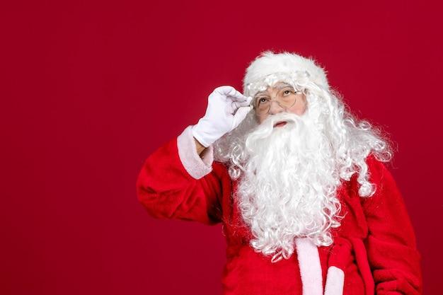 Vista frontal de santa claus con el clásico oso blanco y ropa roja en la emoción de año nuevo de navidad de vacaciones rojas