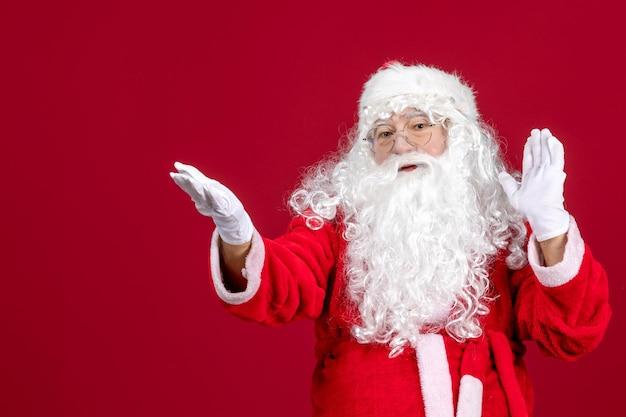 Vista frontal de santa claus con el clásico oso blanco y ropa roja en las emociones de año nuevo de navidad de vacaciones rojas
