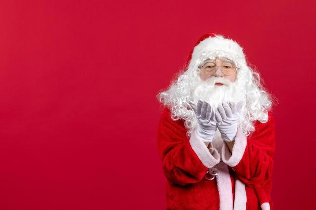 Vista frontal de santa claus con el clásico oso blanco y ropa roja enviando besos en las vacaciones de año nuevo de navidad roja
