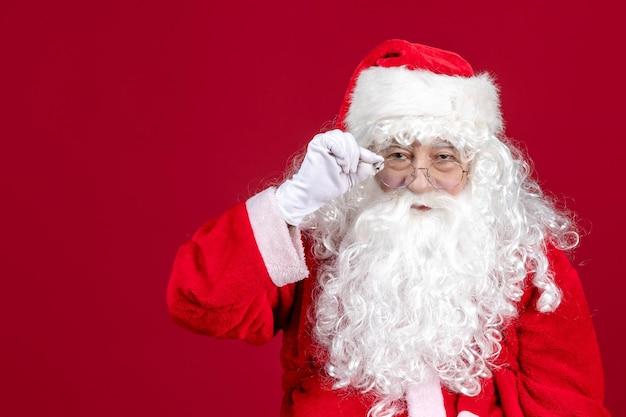 Vista frontal de santa claus con el clásico oso blanco y ropa roja en el escritorio rojo emoción de vacaciones de año nuevo de navidad