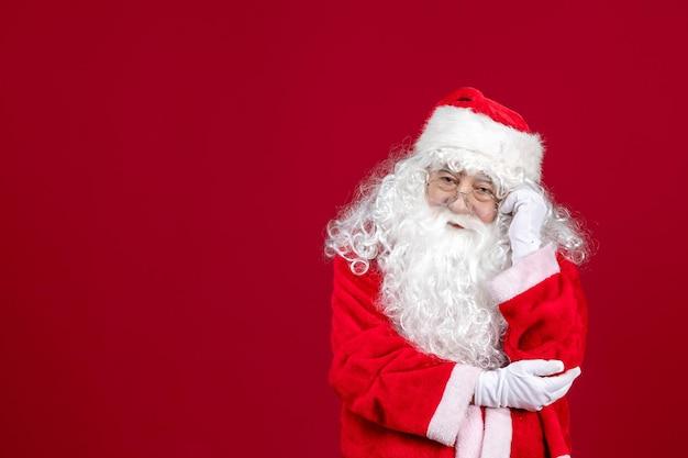 Vista frontal de santa claus con el clásico oso blanco y ropa roja en el escritorio rojo vacaciones navidad año nuevo