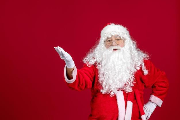 Vista frontal de santa claus con el clásico oso blanco y ropa roja en una fiesta roja de navidad año nuevo