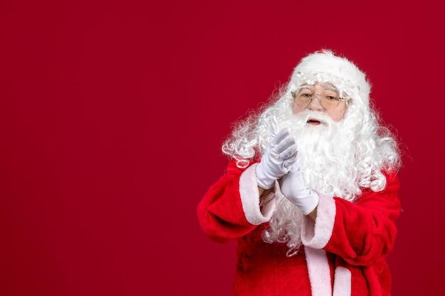 Vista frontal de santa claus con el clásico oso blanco y ropa roja de pie en el escritorio rojo navidad año nuevo