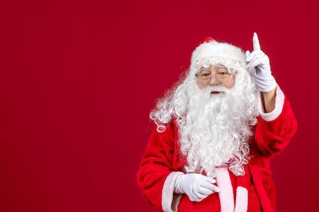 Vista frontal de santa claus con el clásico oso blanco y ropa roja de pie en las vacaciones de año nuevo de navidad rojo