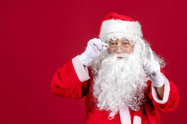 Vista frontal de santa claus con el clásico oso blanco y ropa roja en el piso rojo emoción de vacaciones de año nuevo de navidad