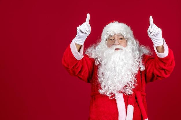 Vista frontal de santa claus con clásico oso blanco y ropa roja en piso rojo vacaciones año nuevo emociones navideñas