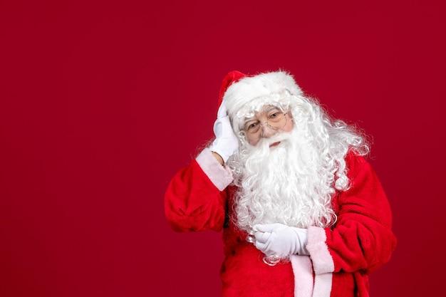 Vista frontal de santa claus con el clásico oso blanco y ropa roja en el piso rojo vacaciones navidad año nuevo emociones