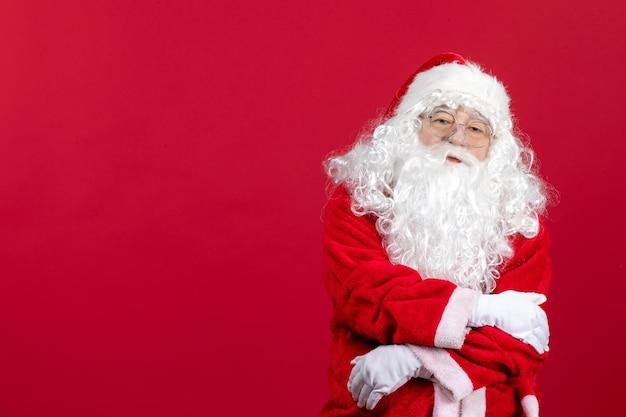Vista frontal de santa claus con el clásico oso blanco y ropa roja en rojo navidad año nuevo vacaciones
