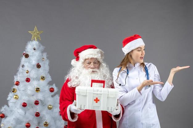 Vista frontal de santa claus con doctora que le dio botiquín de primeros auxilios en la pared gris
