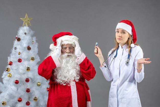 Vista frontal de santa claus con doctora que sostiene el dispositivo de medición de temperatura en la pared gris