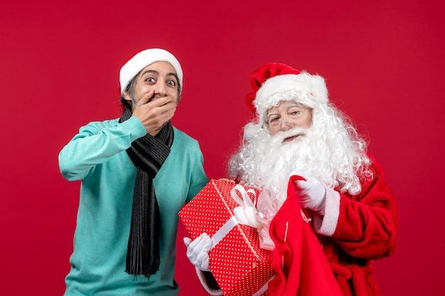 Vista frontal de santa claus con hombre sacando el presente de la bolsa en color rojo de emoción de navidad de vacaciones