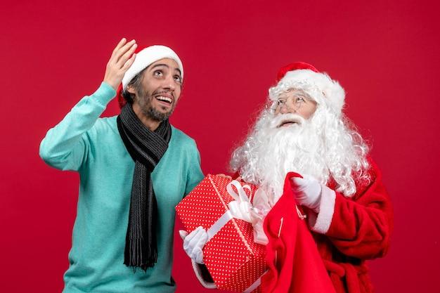 Vista frontal de santa claus con hombre sacando el presente de la bolsa en color rojo de emociones navideñas de vacaciones