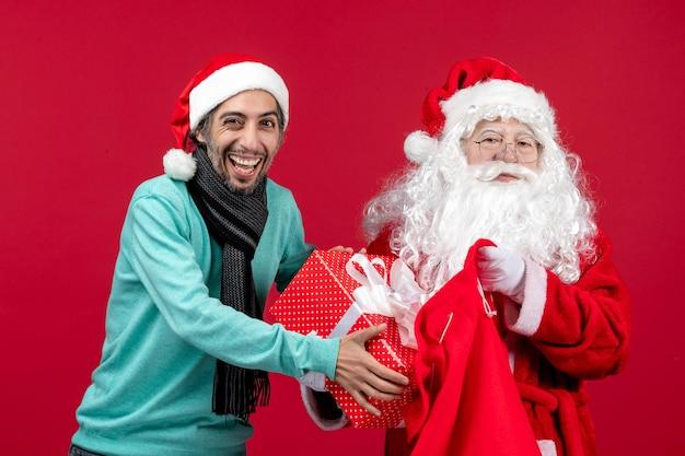Vista frontal de santa claus con hombre sacando el presente de la bolsa en color rojo de vacaciones de emociones de navidad