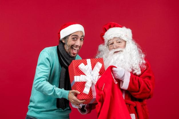 Vista frontal de santa claus con hombre sacando el presente de la bolsa en la emoción de navidad de vacaciones rojas