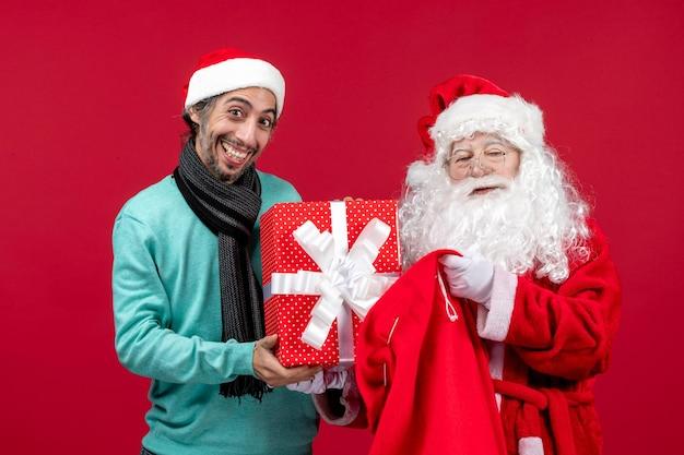 Vista frontal de santa claus con hombre sacando el presente de la bolsa en rojo emoción de navidad color rojo